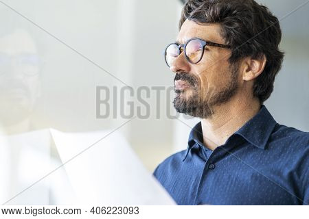 Business Man Wearing Glasses  Holding Paper Document Looking At The Window. Successful Male Portrait