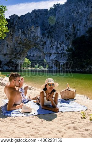 Couple Men And Woman Visiting The Famous Natural Bridge Of Pont Darc In Ardeche Department In France