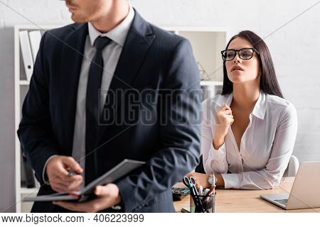 Seductive Businesswoman At Workplace Looking At Colleague Holding Notebook On Blurred Foreground.
