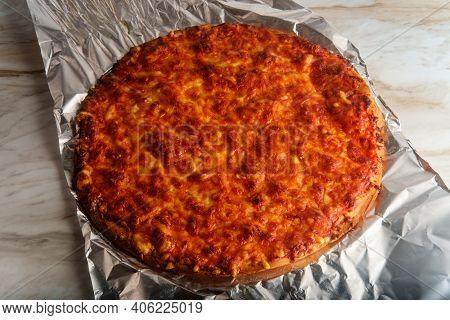Unsliced Crispy Nyc Style Pizza Pie On Tin Foil