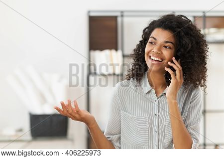 Happy African American Teenage Girl With Curly Hair Talking On Mobile Phone And Laughing As She Did