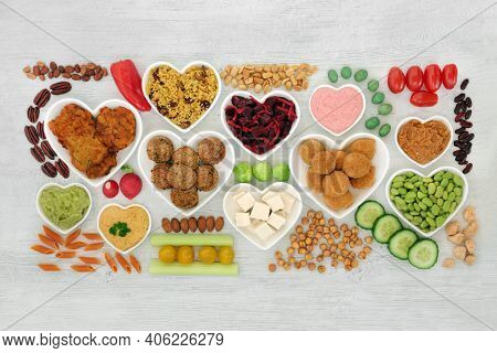 Vegan health food for ethical eating with plant based foods high in protein, fibre, antioxidants, anthocyanins, vitamins, minerals, omega 3, smart carbs. Heart health foods. On rustic wood. Flat lay.