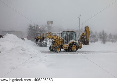 NORWALK, CT, USA-FEBRUARY 1, 2021:  Snow plow machinery  during snow storm  day cleaning parking lot on shopping plaza