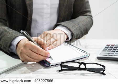 Close Up Woman Hand Holding Pen. Businesswoman Writing In Notepad. Female Accountant Working At Desk