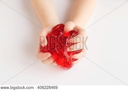 Child Clutching Colorful Red Slime Toy. Kids Hands Playing Slime On White Background. Making Slime.