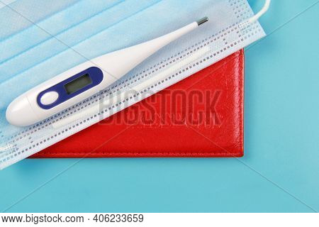 Passport, Thermometer, Disposable Medical Mask On A Blue Background. Global Problems And The Closure