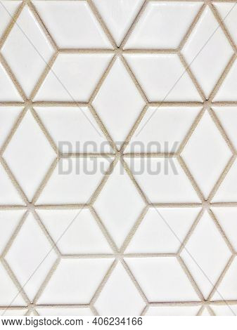 White, Geometric Patterned Wall Tile With Beige Colored Grout Visually Creates An Illusion Of Multip