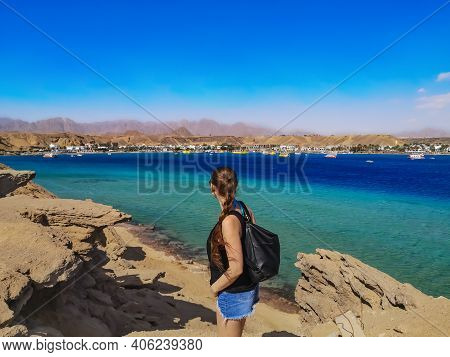 A Young Woman Stands On A Rock And Looks At The Opposite Side Of The Sharm El-maya Bay In Sharm El S