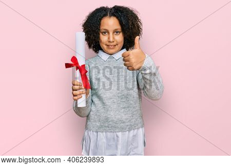 Young little girl with afro hair holding graduate degree diploma smiling happy and positive, thumb up doing excellent and approval sign