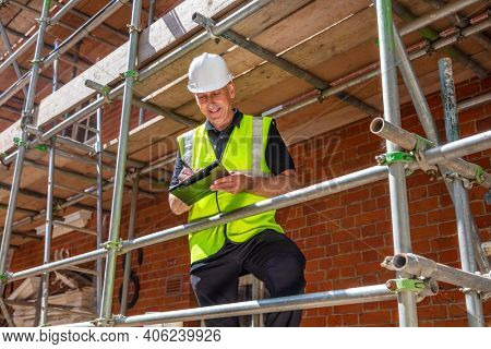 Male builder foreman, construction worker, contractor or architect on building site writing on black clipboard