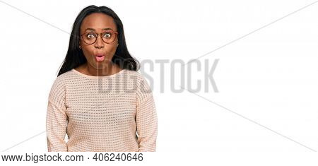 Young black woman wearing casual clothes and glasses scared and amazed with open mouth for surprise, disbelief face