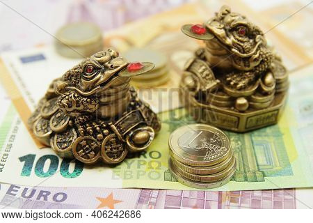 Two Chinese Feng Shui Lucky Money Frogs Sitting On Euro Banknotes. Symbol Of Abundance And Luck