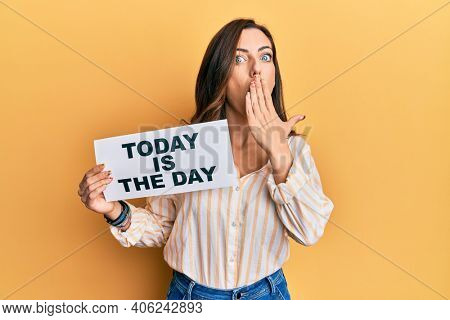 Young brunette woman holding today is the day covering mouth with hand, shocked and afraid for mistake. surprised expression