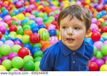An Emotional Face Of Smiling Baby Playing In The Balls Pool. Happy Kid Playing With Colored Balls. C