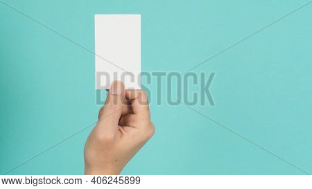 Male Hand Holding White Blank Card Isolated On Green Or Tiffany Blue Background.