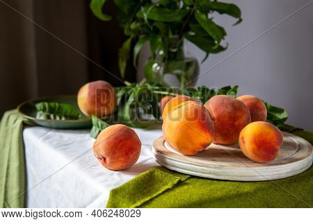 Peaches On Table In Kitchen Near Window. Rustic Minimalism Food Peach Fruits With Leaves On Wooden B
