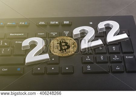 A Gold Bitcoin Is Placed On A Dark-colored Keyboard. The Year 2022 Is Laid Out In Metal Numbers. Clo