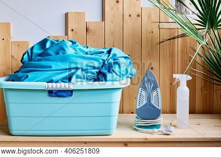 Basket With Clean Laundry, Iron And Spray Bottle On Table At Home. Real Laundry Room With Wooden Wal