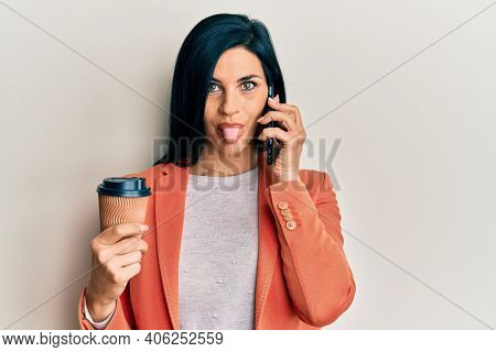 Young caucasian woman having conversation talking on the smartphone holding take away coffee sticking tongue out happy with funny expression.