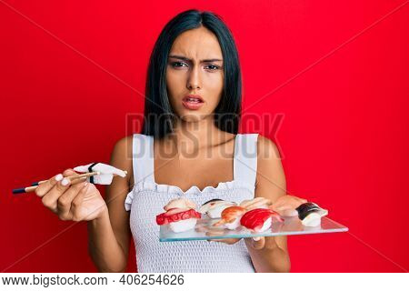 Young brunette woman eating butterfish sushi using chopsticks in shock face, looking skeptical and sarcastic, surprised with open mouth
