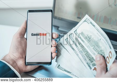Russia Moscow 02.02.21 Mobile Phone With Logo Of Gamestop, Money, Dollars In Hand. Company Making Vi