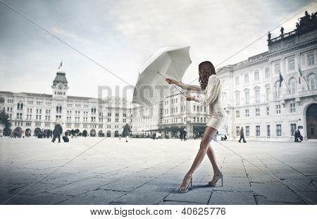 Young woman in white opening a white umbrella