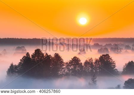 Amazing Sunrise Over Misty Landscape. Scenic View Of Foggy Morning Sky With Rising Sun Above Misty F