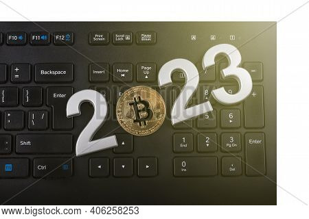 A Gold Bitcoin Is Placed On A Dark-colored Keyboard. The Year 2023 Is Laid Out In Metal Numbers. Clo