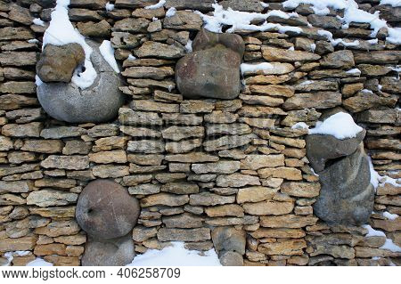Sandstone Wall With Inserts Of Large Stone And A Little Snow. Texture Of Sandstone Walls. Sandstone