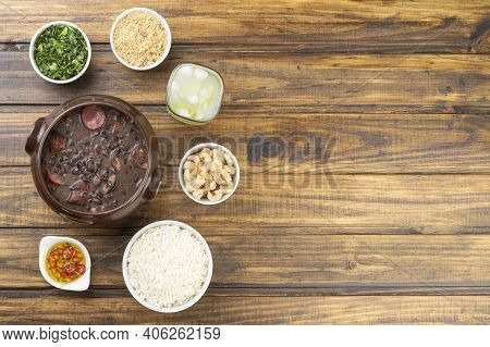Traditional Brazilian Feijoada With Manioc Flour, Kale, Caipirinha, Rice, Cracklings And Copy Space.