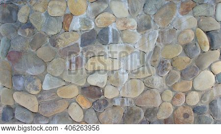 Wall Built Of Rounded Colored Stones. Texture Of Rounded Colored Stone Walls. Rounded Colored Stone