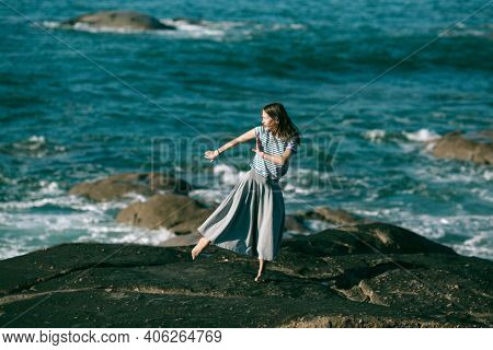 The dancer woman is engaged in choreography on the rocky Alantic ocean coast.