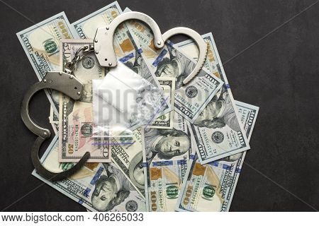 Money, Drugs And Handcuffs. Handcuffs, Money And Cocaine Drugs On Dark Background Close Up
