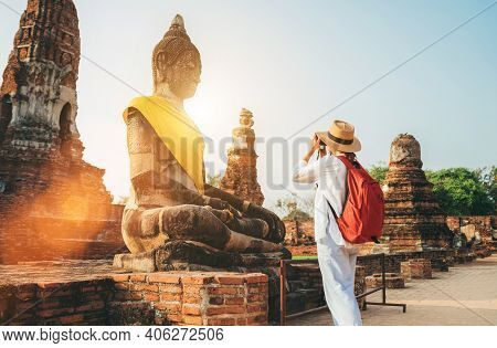 Solo Traveler Woman With A Backpack Taking A Photo Of Seated Buddha Statue At Wat Ratchaburana Or Wa