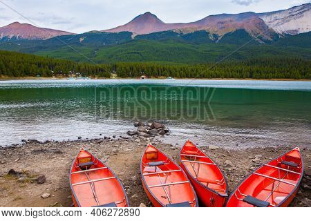 Red boats - canoes are dried on the shore of the lake. Maligne Lake in Jasper, located in the Canadian Rockies. The lake is surrounded by mountain peaks. Autumn travel to Canada.