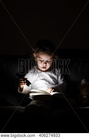 Toddler Caucasian Girl Reading Book At Hight With Flashlight. Unplugged Childhood Activities. Goodni