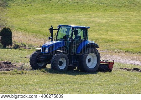 Blue Tractor Ready For Field Work But Without Driver On A Green Meadow, Photographed From Front Side