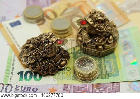 Two Chinese Feng Shui Frogs Sitting On Euro Banknotes. Symbol Of Abundance And Luck.