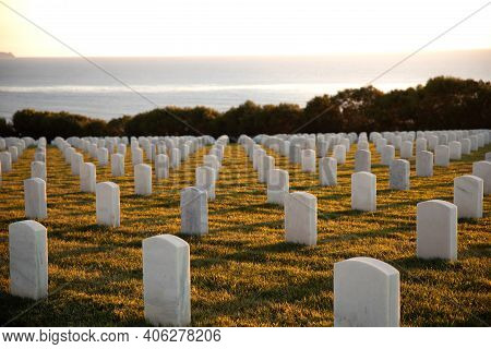 War Cemetery With Rows Of White Marble Graves On Green Grass At Sunset With Ocean View. Marine Veter