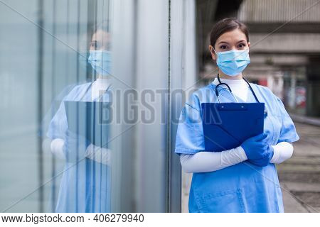 Young Female Nhs Uk Ems Doctor In Front Of Healthcare Icu Facility,wearing Protective Face Mask Hold