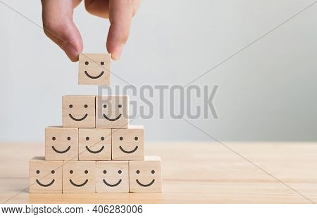 Hand Putting Wooden Cube Block Shape With Icon Face Smiley, The Best Excellent Business Services Rat