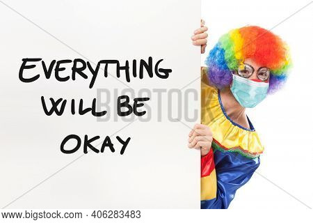 Clown wearing a mask showing panel with text Everything will be okay, coronavirus funny concept