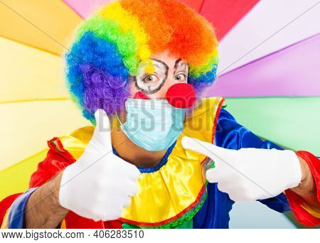 Masked positive clown giving thumbs up, covid coronavirus concept