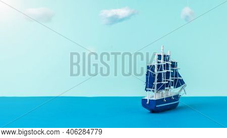 A Sailboat With Blue Sails Sailing Away From The Shore. The Concept Of Travel And Adventure. Install
