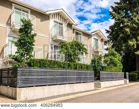 Residential Condo Building With Fenced Front Yard On Bright Sunny Day