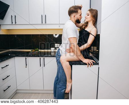 Young Couple At Home. Preparing Meal Together. Happy Loving Young Couple Newlyweds Enjoy Cooking Sup