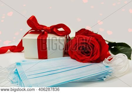The Gift Box Is Tied With A Bright Scarlet Ribbon, Rose Flower And Protective Face Masks On A White