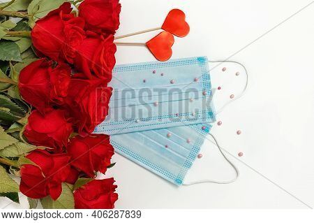 A Bouquet Of Bright Scarlet Roses And Protective Face Masks On A White Background, The Concept Of Ce