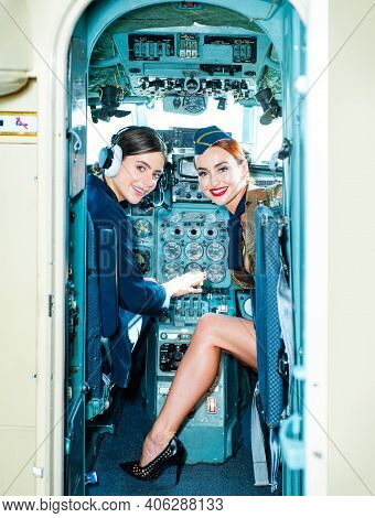 Women Pilot And Flight Instructor In Aircraft Cockpit. Beautiful Smiling Young Women Pilots Sitting