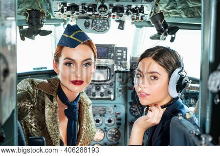 Pilots Sitting In Cabin. Young Woman With Headset. Portrait Of Two Attractive Young Women Pilots Wit